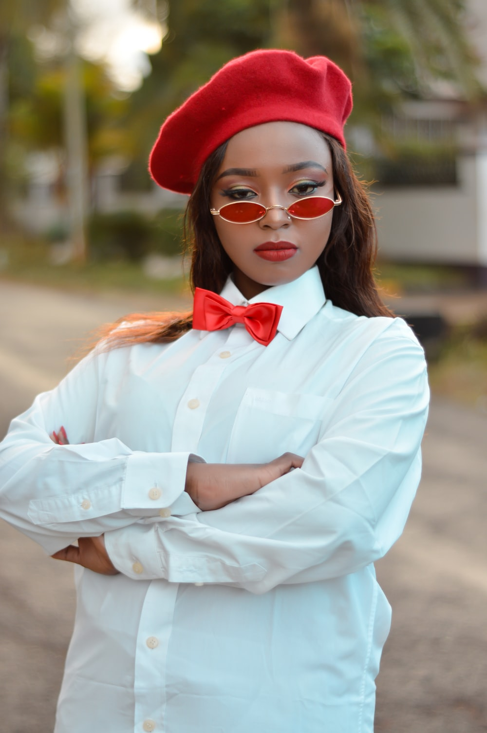woman wearing white dress shirt and red cap