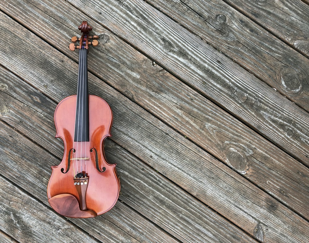 closeup photo of violin on brown surface