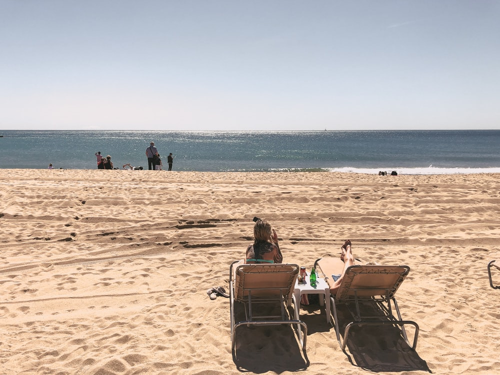 two women on brown lounger chairs beside seashore during daytime
