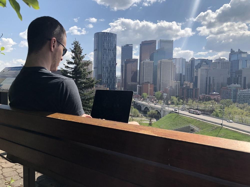 man wearing grey shirt sitting on bench using laptop