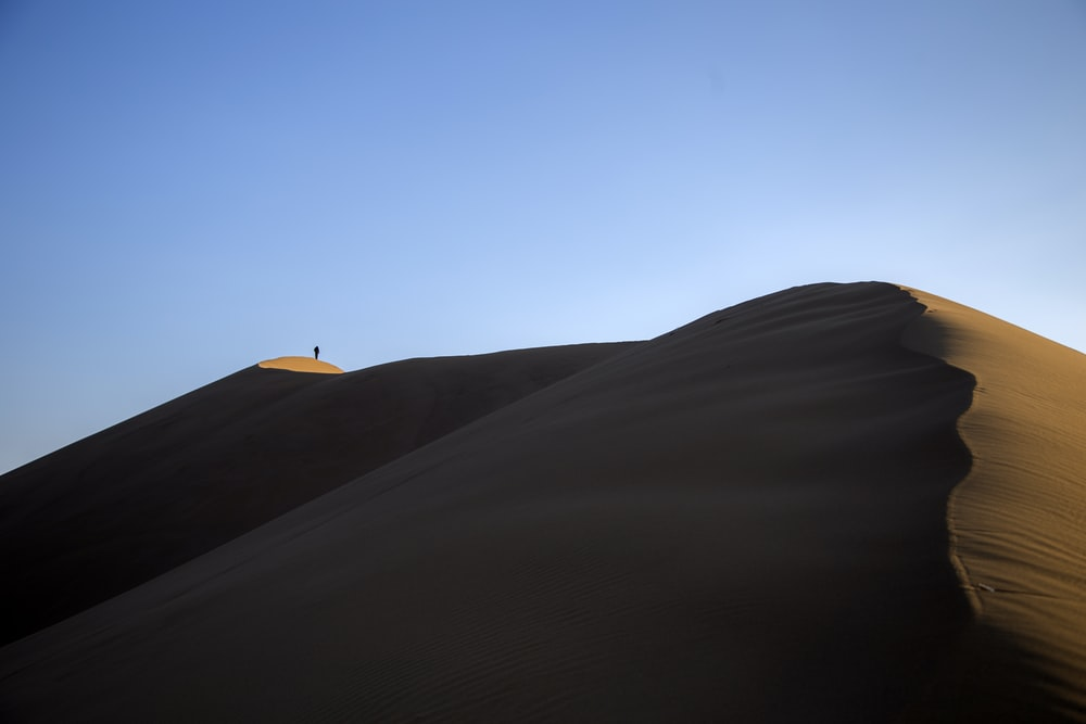 person standing on sand hill