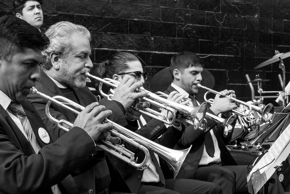 greyscale photo of trumpet players playing