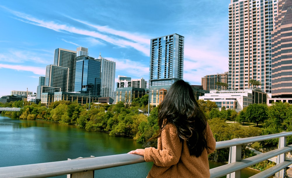 woman holding handrail overlooking cityscape during daytime