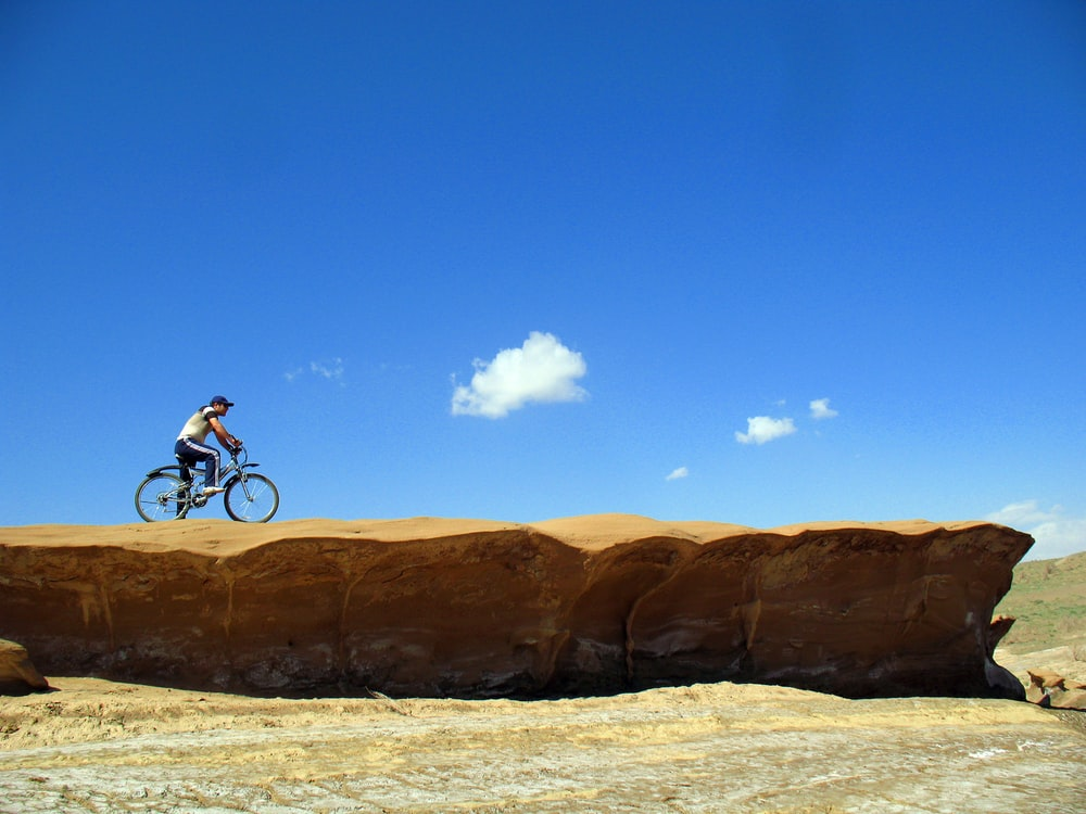 man riding bike on rocky mountain during day