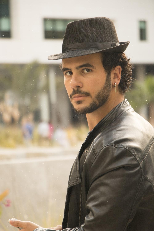 man in grey leather jacket and black hat looking over left shoulder