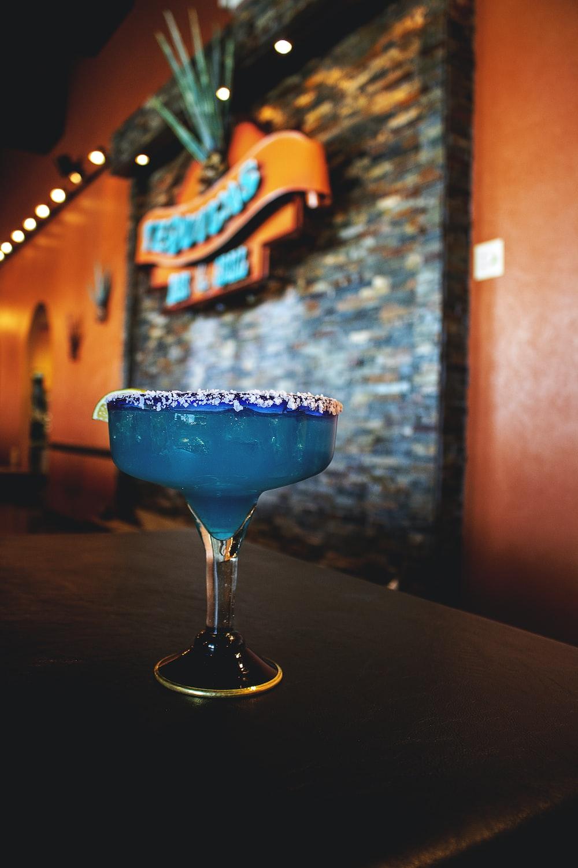 glass of blue margarita on table