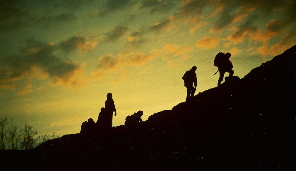 silhouette of people trekking during golden hour