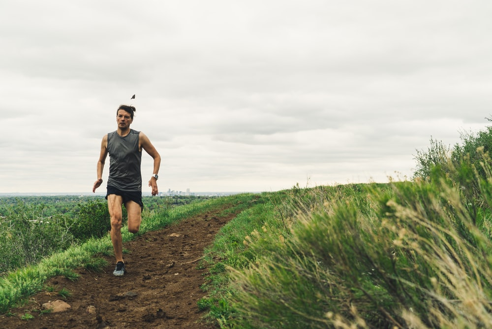 man wearing gray tank top running during daytime