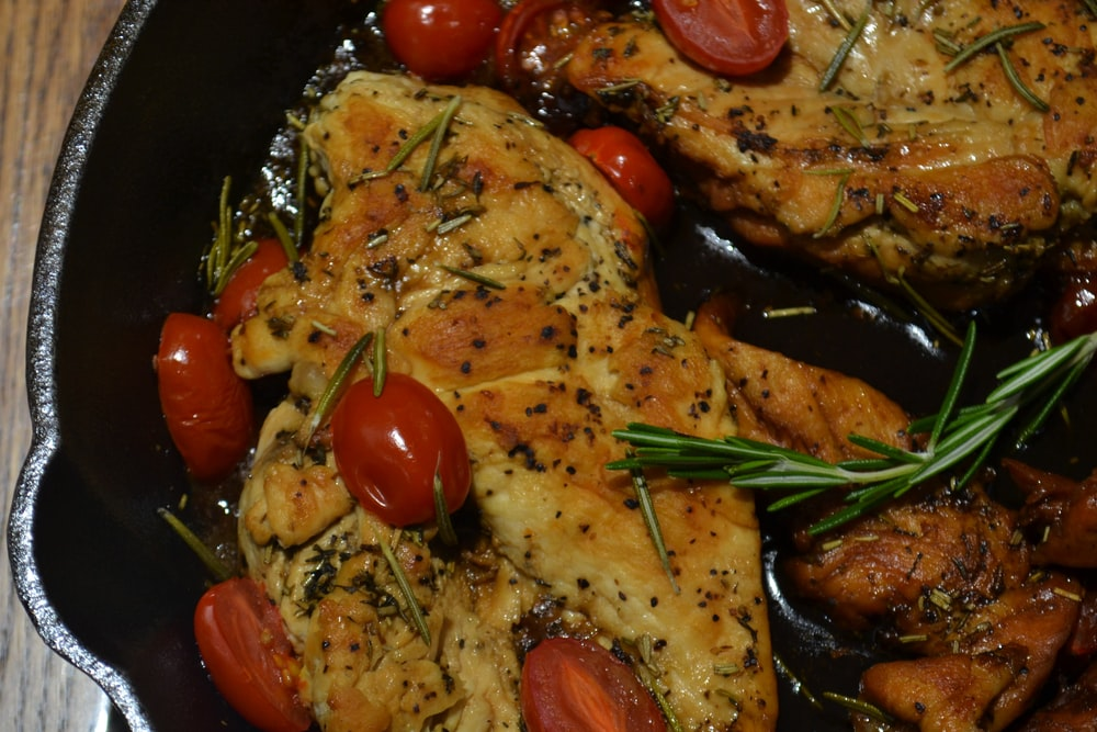 cooked meat with sauce garnish with tomatoes and dill