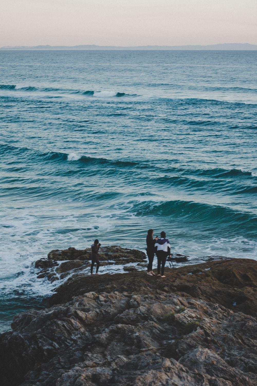 three people standing near beach cliff viewing blue calm sea
