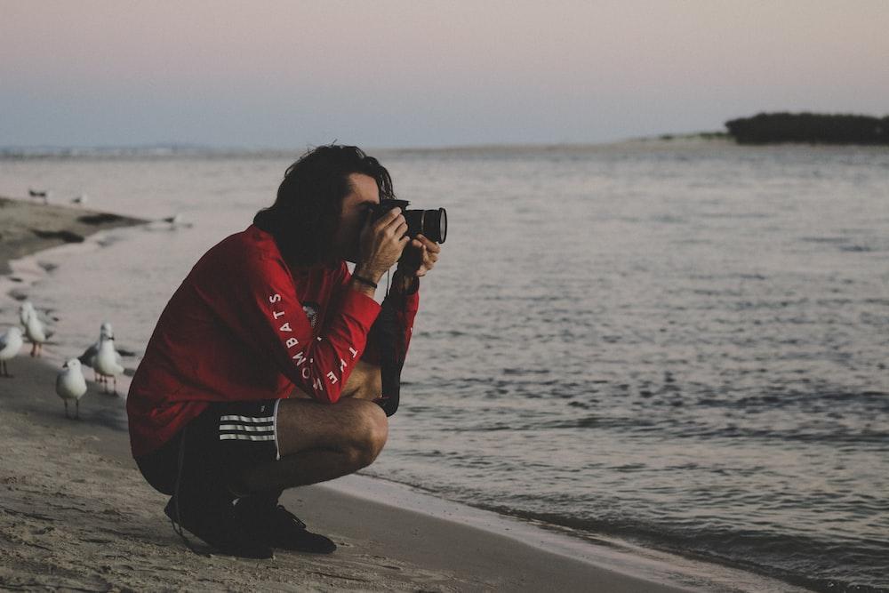 man sitting on the seashore taking photo