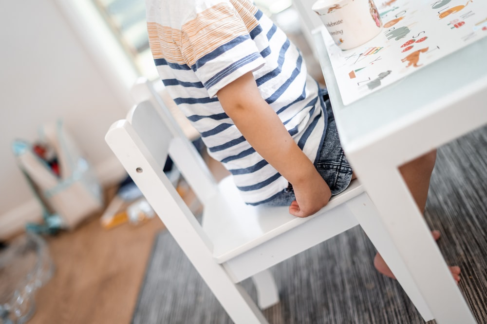 child sitting on white chair near table