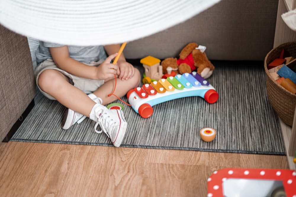 child sitting on floor and playing with xylophone toy