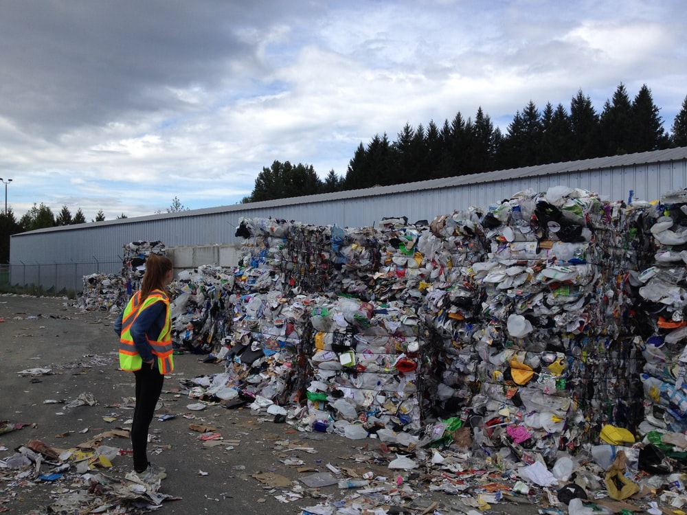 woman standing in front garbage