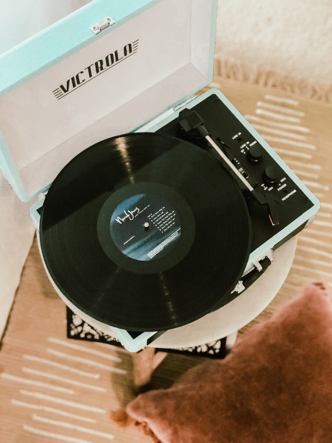 Victrola turquoise suitcase record player playing a black record in a bedroom.