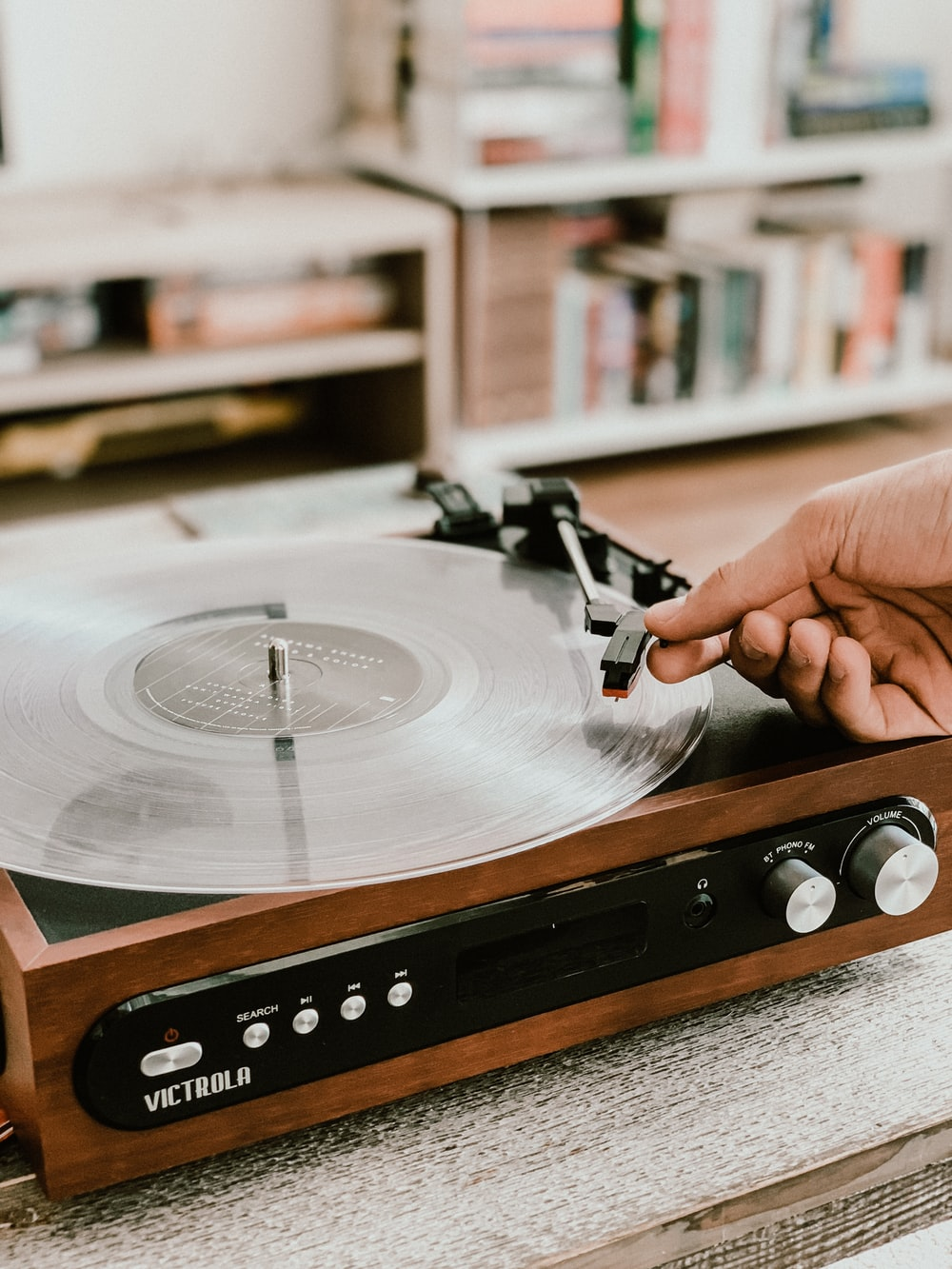 person playing record on Victrola turntable