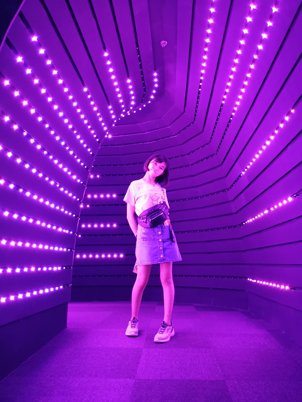 woman standing in middle of purple lighted passage