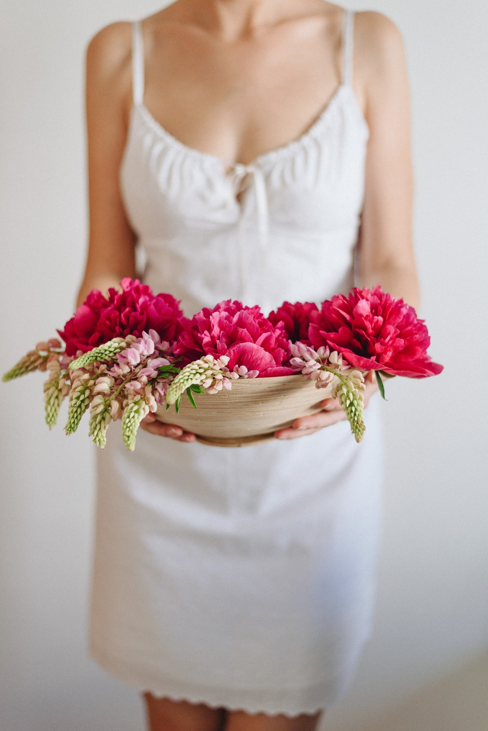woman in white dress carrying red flowers