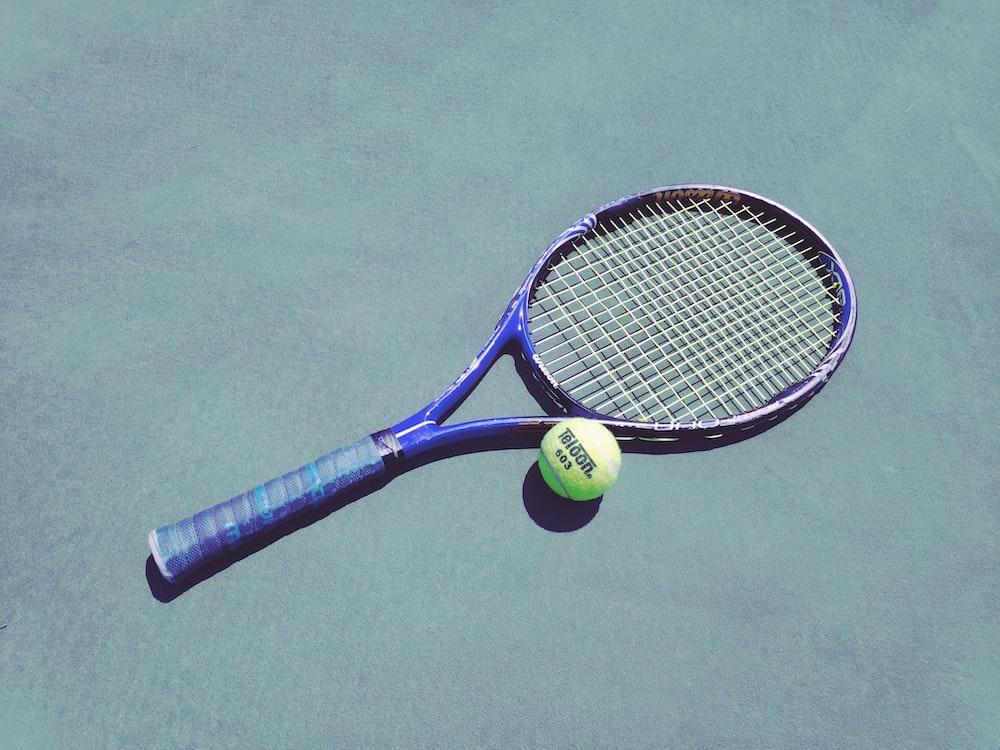 blue tennis racket and green Wilson ball