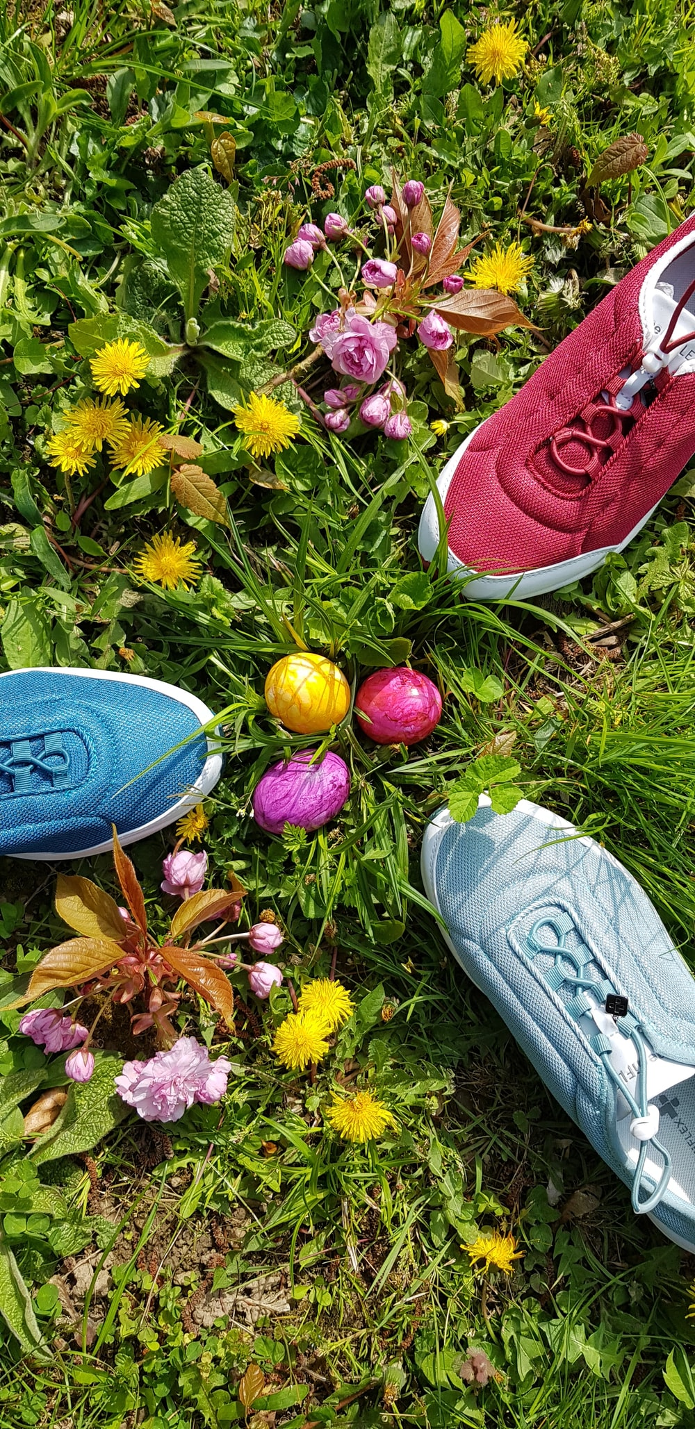 three assorted-color shoes near Easter eggs on green field