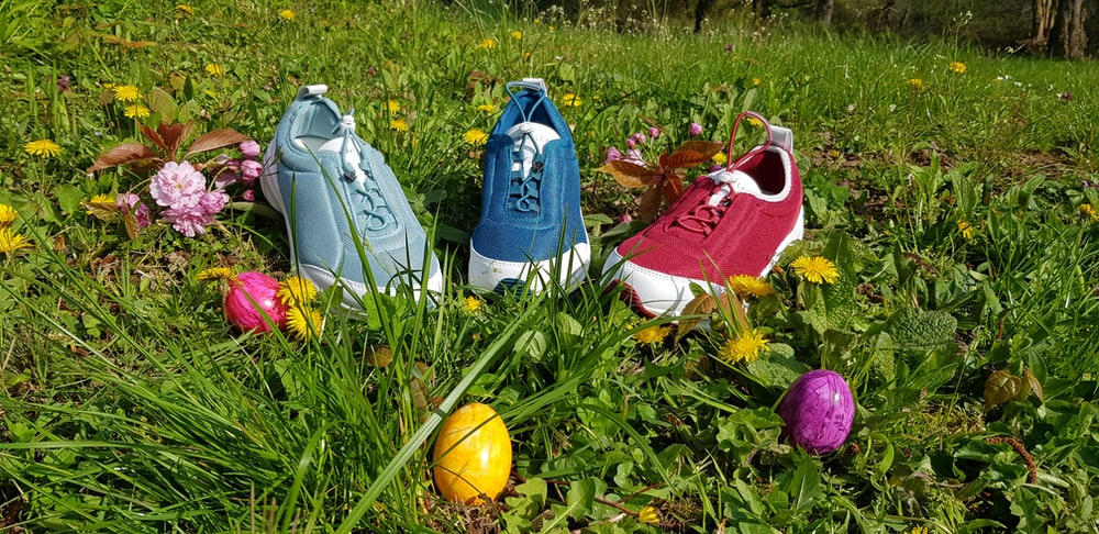 three assorted-color sneakers on grass