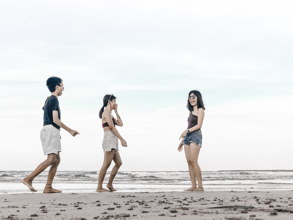 three persons standing on shore