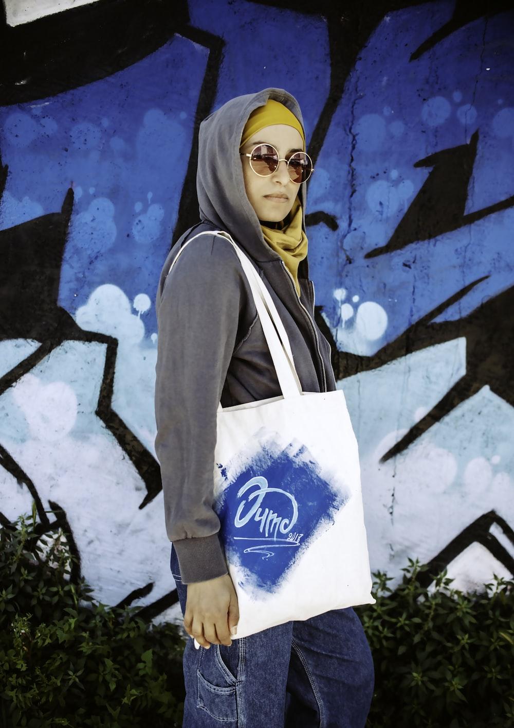woman wearing grey hoodie carrying white shoulder bag