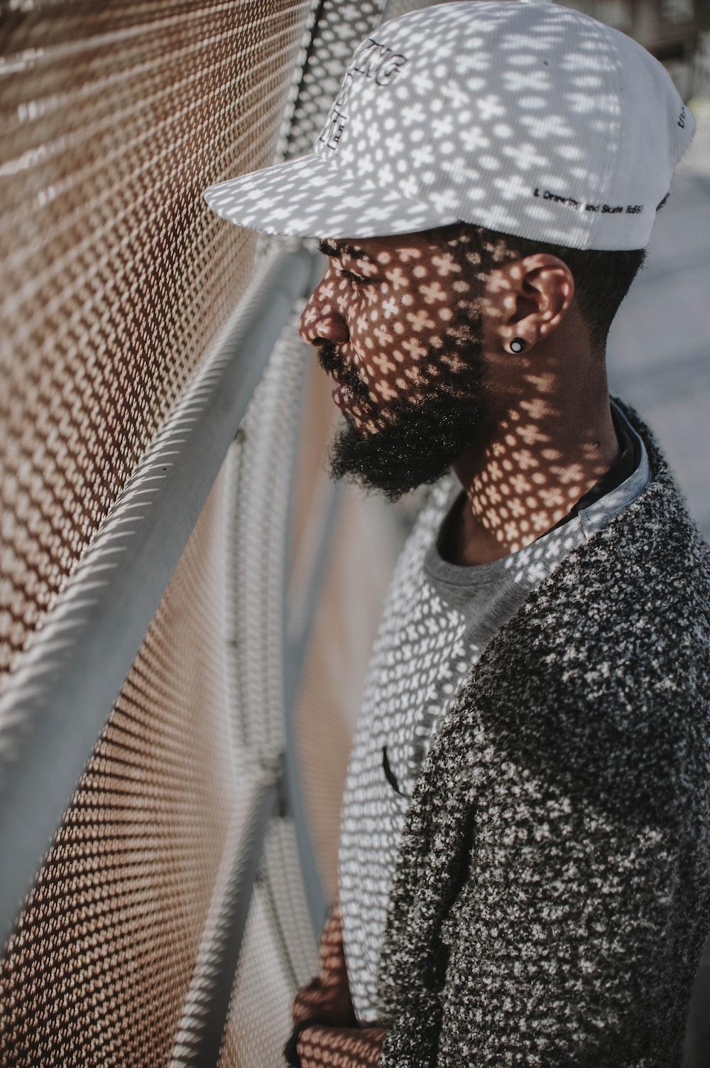 man facing white screen fence