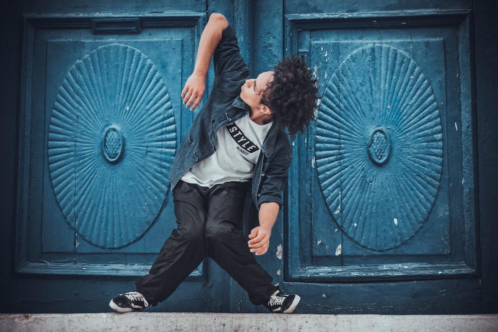man doing stunt in front of blue door