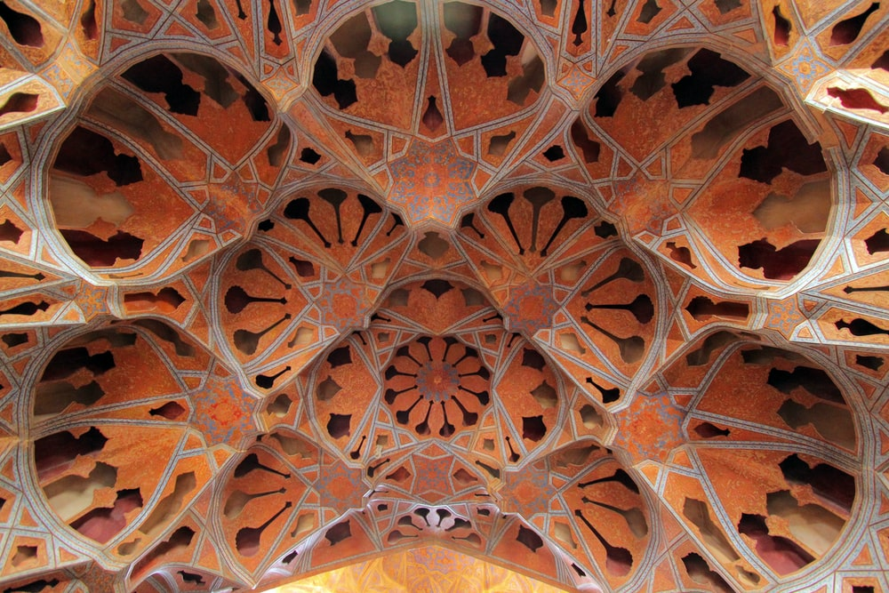 low-angle photography of orange and black geometric ceiling