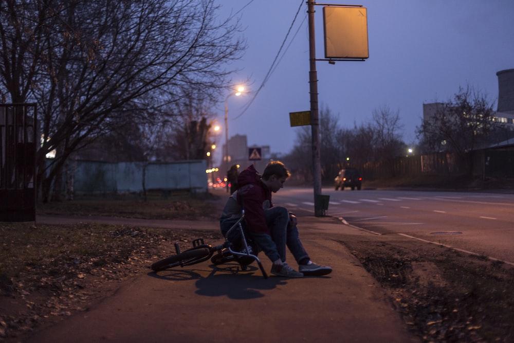 man sitting on sidewalk during nighttime