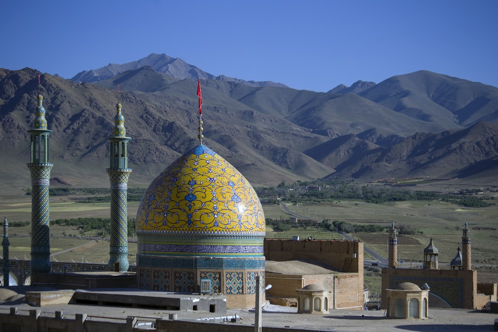 close photo of mosque near mountain