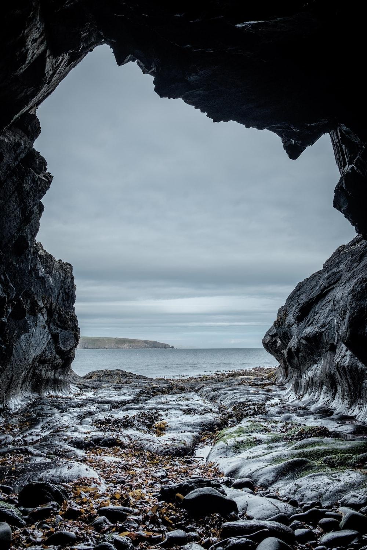 gray rock formation beside beach