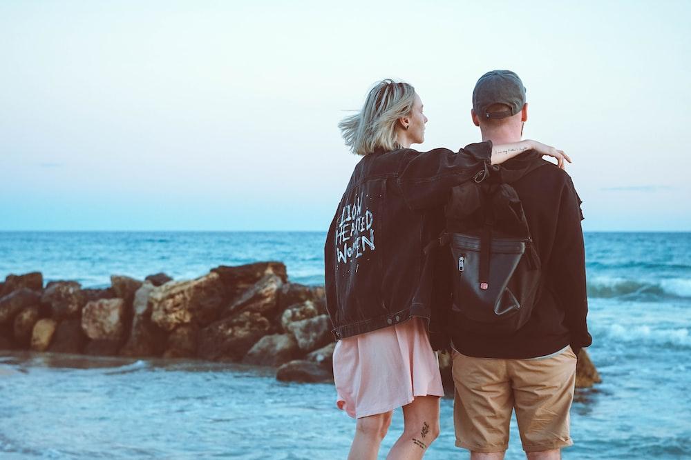 man and woman standing near beach line