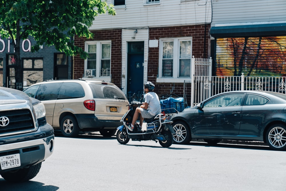 man riding scooter on road during daytime