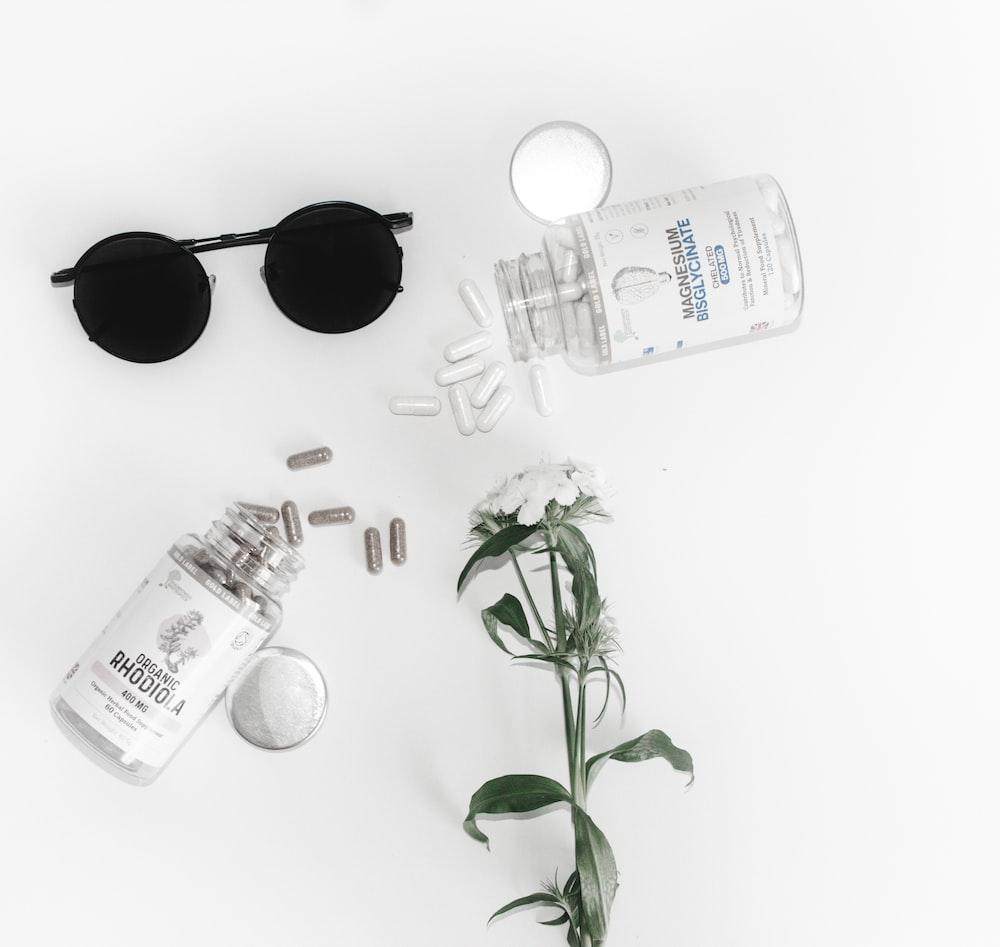 black framed hippie sunglasses beside glass bottle