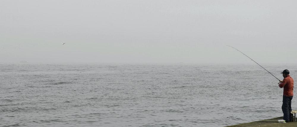 man fishing beside sea
