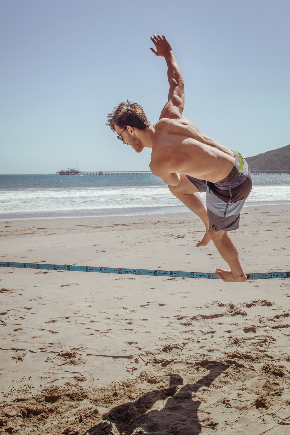 man in sunglasses and board shorts walking on rope