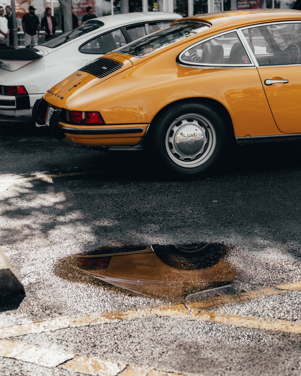 classic orange coupe near puddle of water on road during daytime