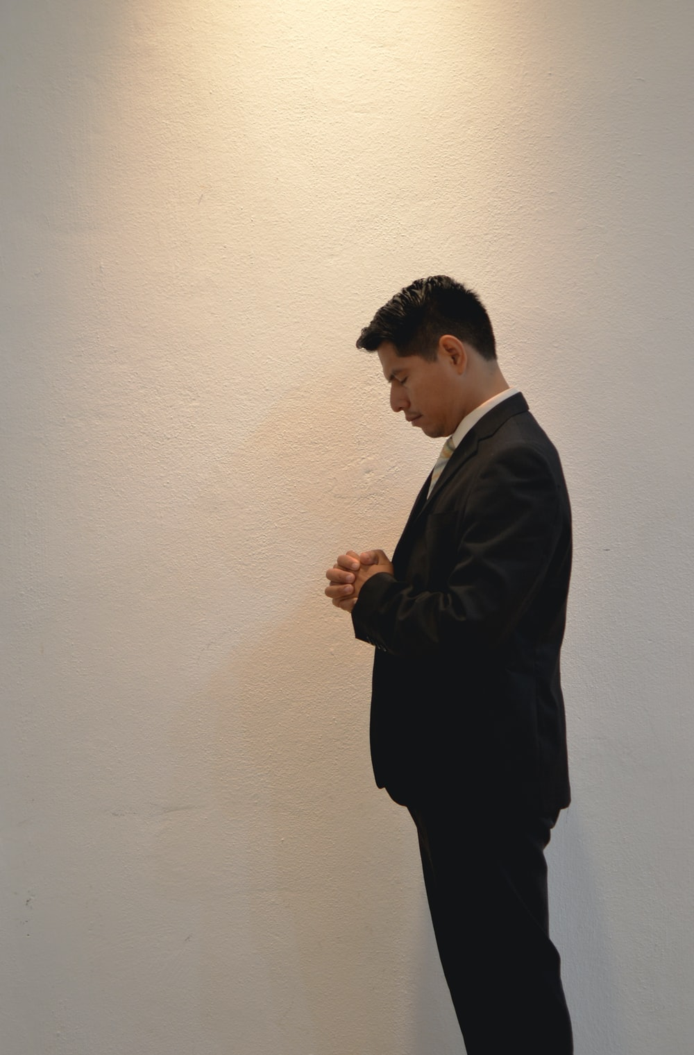 man prays in front white painted wall