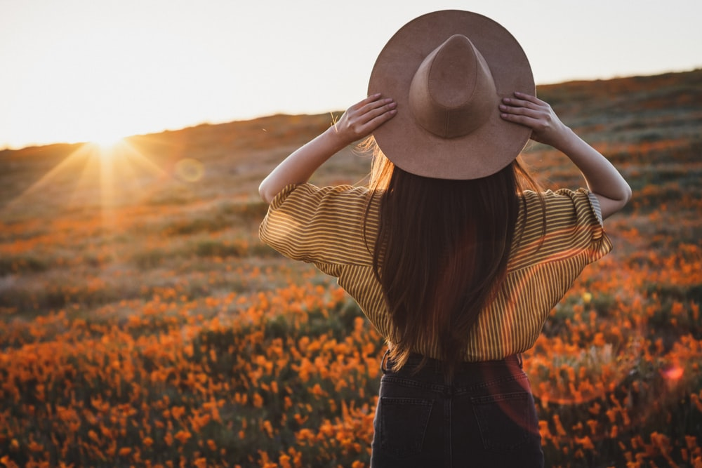 woman wearing yellow shirt and black bottoms and brown hat during golden hour
