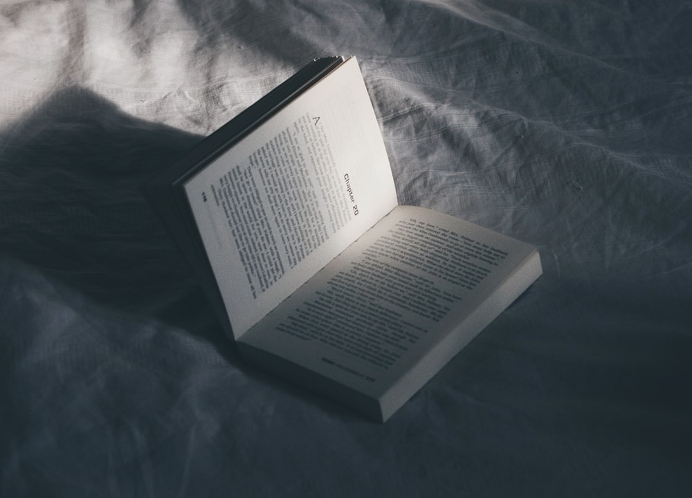 opened book on bed