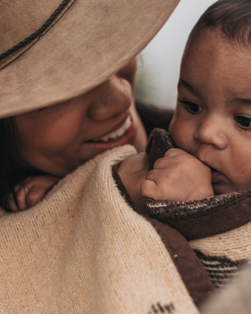 woman in hat carrying baby
