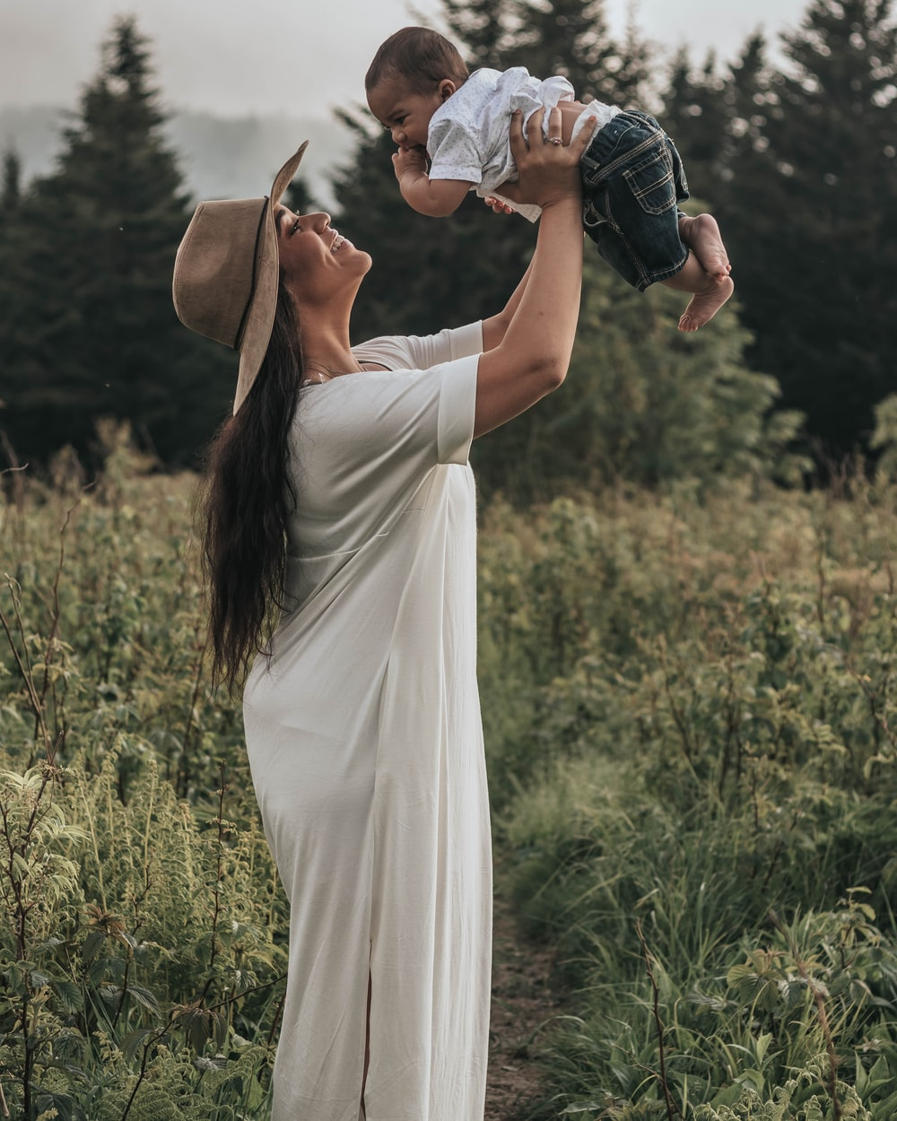 woman standing while holding baby