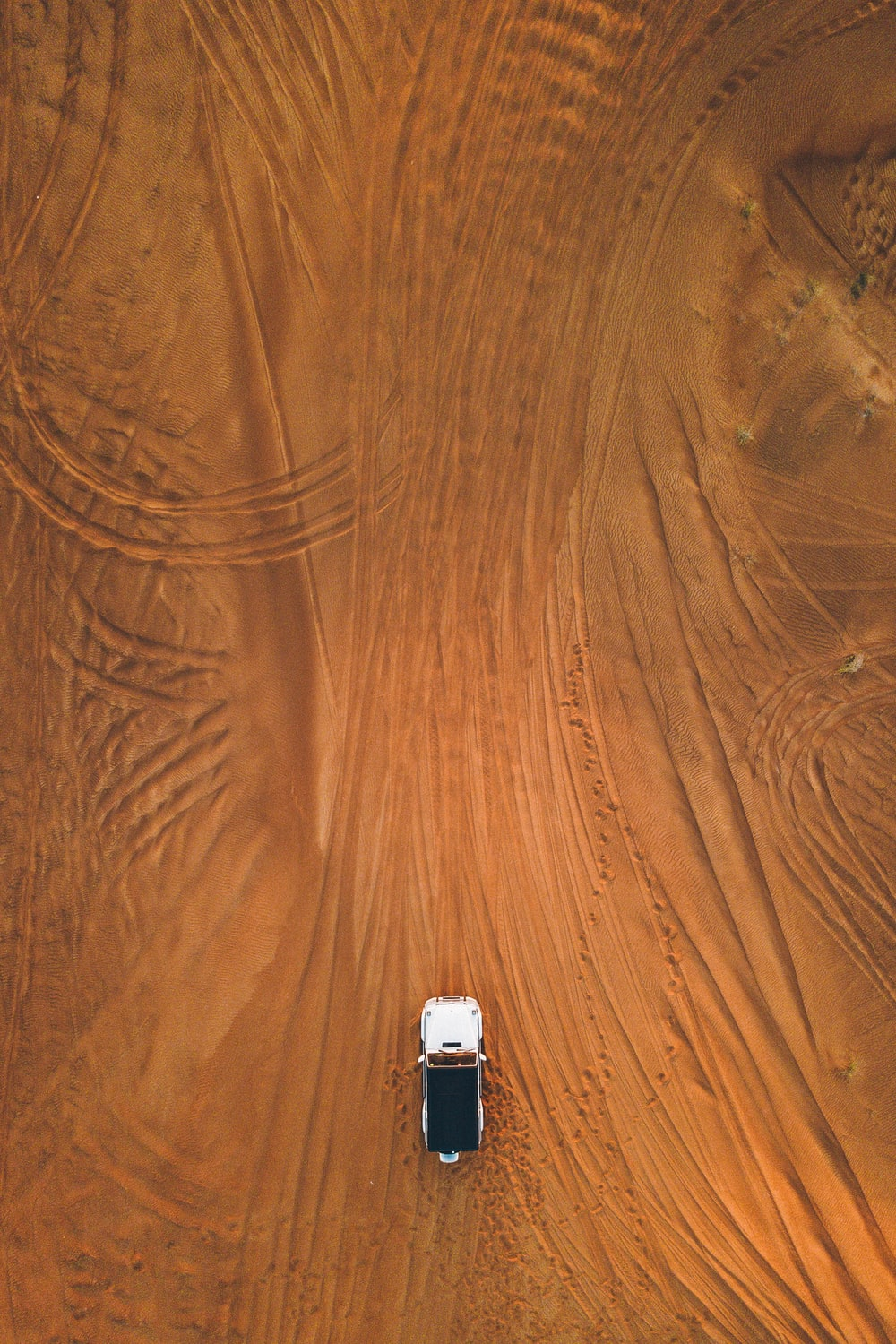 aerial photography of white SUV cruising on sand