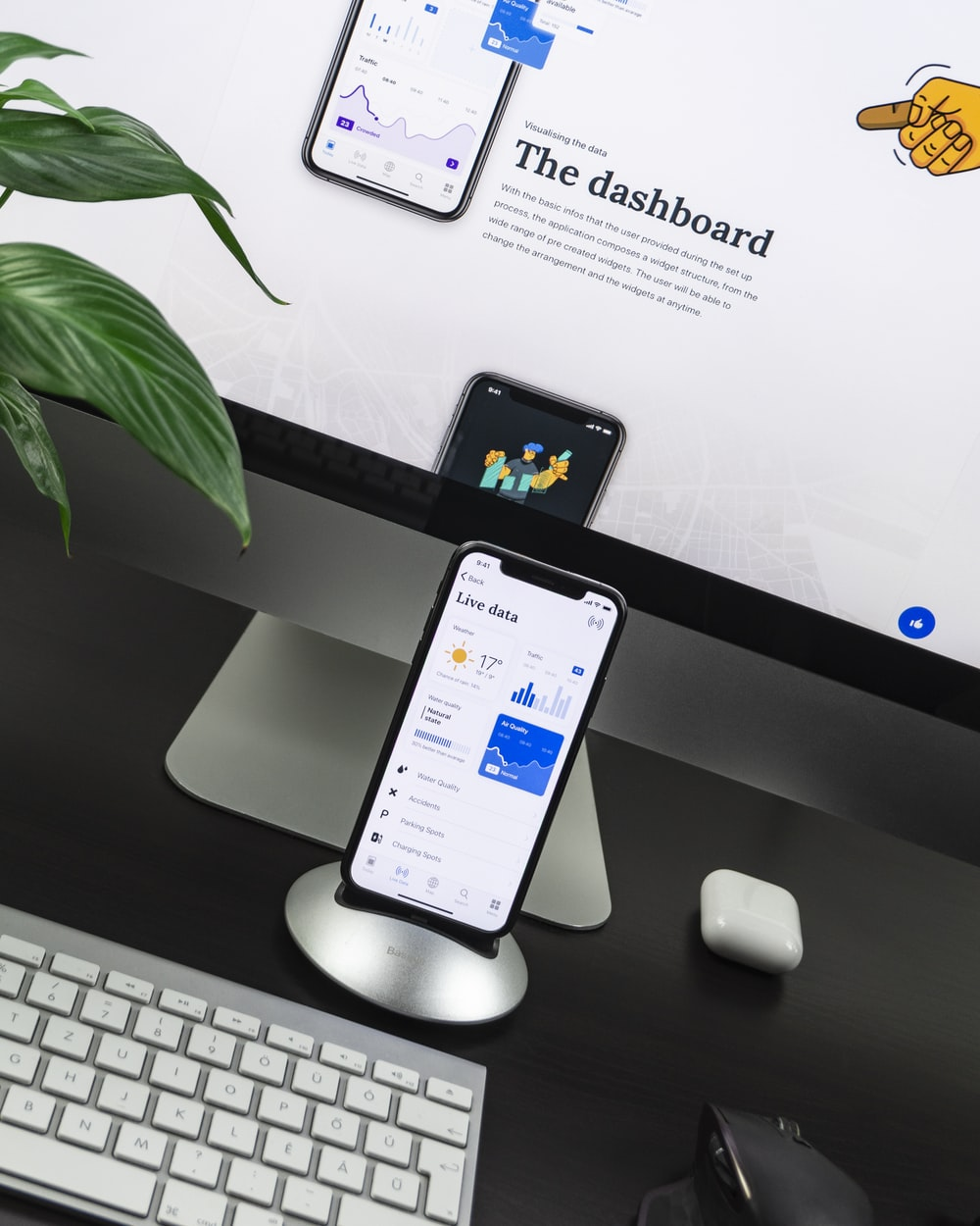 space gray iPhone X on stand near silver iMac and Apple Magic Keyboard