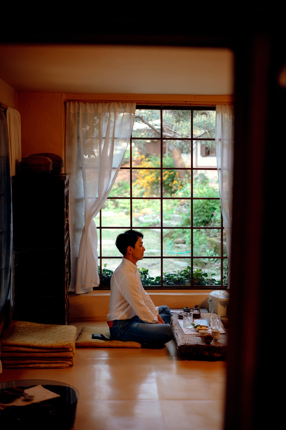 man sitting on floor by table and window