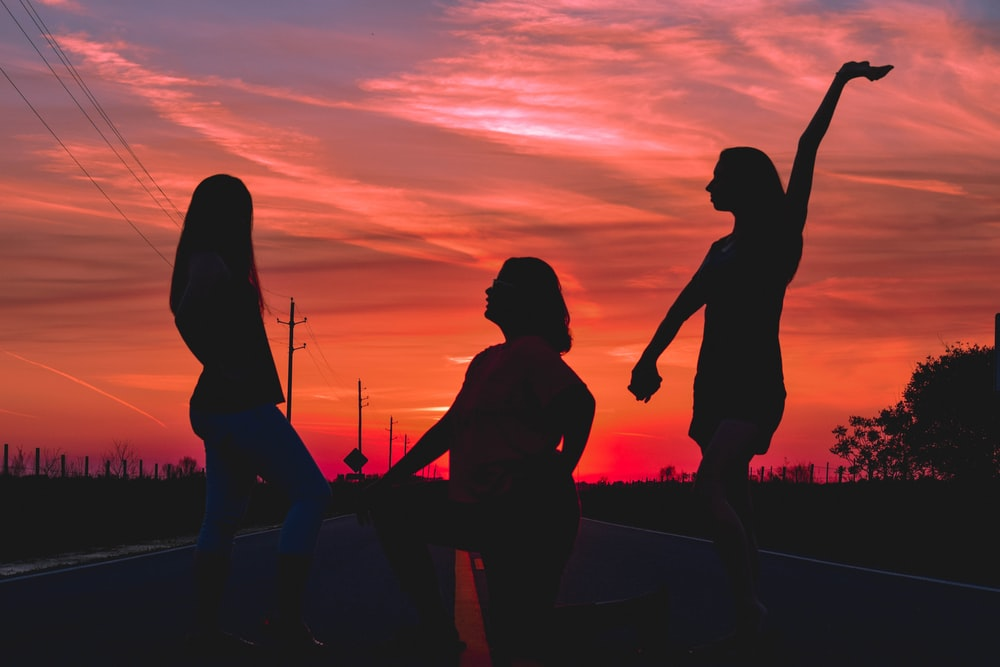 three women posing in the middle of the road during golden hour