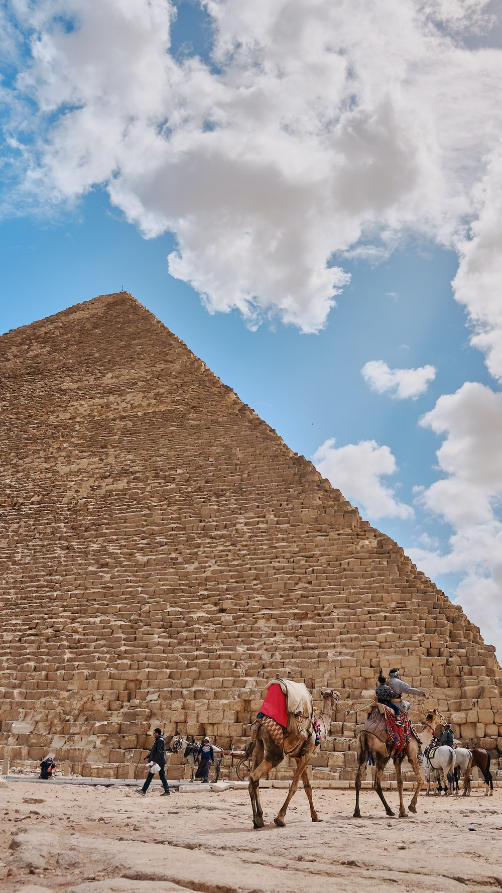 people riding camels by pyramid during daytime