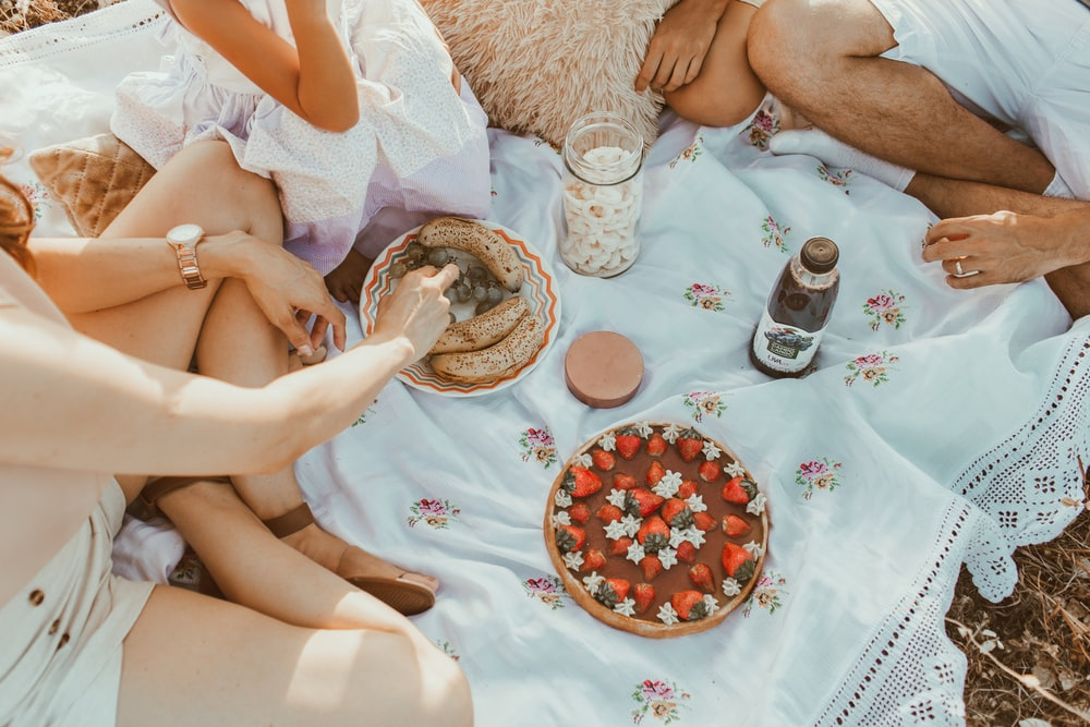 people sitting on white textile eating bread near cake